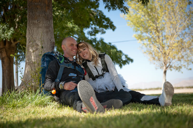 evgeny and emily smiling together under a tree on their skydiving wedding day